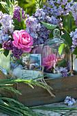 Sträuße mit Rosenblüten und Flieder in Holzkiste