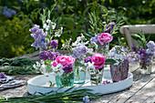 Kleine Sträuße aus Rosen, Flieder, Nachtviole und Gräsern auf Holztablett