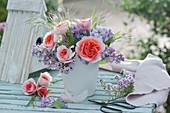 Kleiner Strauß aus Rosen und Flieder, blühender Zweig von Thymian und Schere