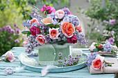 Strauß aus Rosen und Flieder im Filzmantel als Tischdeko