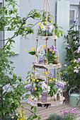 Selbstgebaute Etagere aus Birkenscheiben: Sträuße aus Fliederblüten und Hahnenfuß