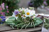 Kleine Tischdeko mit Wiesenblumen: Margeriten, Witwenblume, Wildrose und Graskranz