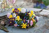 Kränzchen mit Blüten von Narzissen, Primeln, Tausendschön und Vergißmeinnicht
