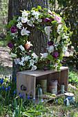 Kranz mit Tulpen, Radspiere, Ranken und Zweigen an Baumstamm gelehnt, Holzkiste mit Garnrollen und Glasglocke