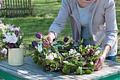 Frau steckt Tulpen in Kranz mit Radspiere, Ranken und Zweigen