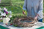Frau windet Kranz aus Ranken und Zweigen, Krug mit Tulpen
