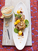 Pork fillet with peanut sauce and spinach and mango salad