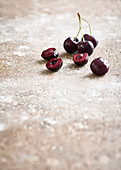 Cherries with drops of water, whole and halved on a stone surface