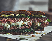 Burger with minced meat, mozzarella, spinach and pine nuts