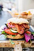 Burger mit Bacon, Tomate und Gurke