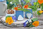 Becher mit Obatzder, Brezeln, Schnittlauch, Blüten von Kapuzinerkresse und Hornveilchen auf Holzbrett aus Birkenholz, Holz-Herzen als Deko