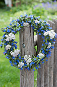 Blau-weißer Kranz aus Natternkopf und Schafgarbe am Zaun
