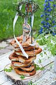Selbstgebauter Brezenturm aus Holzscheibe und Ast, dekoriert mit Kräuter-Kränzchen, Bändern, Birkenscheibe mit Aufschrift Servus und Brezel