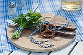 Brotzeitbrett mit Sträußchen aus Petersilie und Schnittlauch, Besteck und Brezel