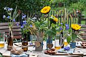 Tischdekoration für bayrische Brotzeit mit Storchschnabel und Getreideähren in Bierflaschen,Sonnenblumen, Besteck im Bierkrug mit Holz-Herz als Deko