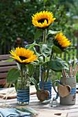 Tischdekoration mit Sonnenblumen, Holz-Herzen und Besteck im Bierkrug