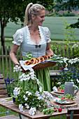 Frau deckt Tisch für die bayrische Brotzeit: Teller mit Radieschen und Brezeln auf Holzscheiben, Bierkrug