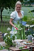 Frau deckt Tisch für die bayrische Brotzeit: Teller mit Radieschen und Brezeln auf Holzscheiben, Topf mit Schnittlauch und Bierkrug