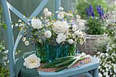 Sträuße aus Rosen, Kamille, Borretsch und Zwiebeln in Gläsern im Gläserträger