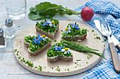 Kleiner Brotzeit-Teller mit herzförmigen Broten mit Butter, Schnittlauch und Blüten von Borretsch und Kamille