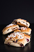 Milk buns with cranberries and nib sugar against a black background