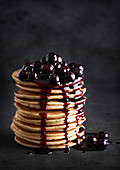 Several stacked pancakes with cherries and cherry sauce