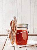 Tomato soup in a mason jar with a mini baguette on a napkin