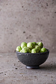 Brussels sprouts in a gray bowl on a stone background