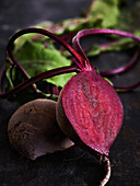 Sliced beetroot with leaves on a black background