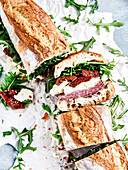 Baguette with salami, mozzarella, dried tomatoes and arugula
