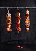 Pork kebabs with peppers and onions hanging on a metal bar