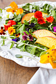 Edible flower-salad with arugula, microgreens and peaches