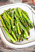 Tray of roasted asparagus on wooden table