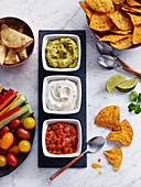 Guacamole, herb curd and salsa with nachos and vegetable sticks