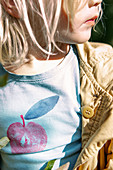 Kind im T-Shirt mit aufgedrucktem Apfelmotiv