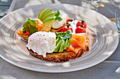 Bread topped with smoked salmon, avocado and poached eggs