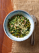 Green spaghettoni with peas, bacon and salsiccia