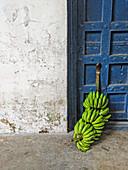 Grüne Bananen an einer alten Tür (Sansibar)