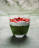 Matcha-Chia-Pudding mit weißer Reismilchschokoladen-Sahne und frischen Erdbeeren