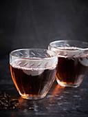 Zwei Tassen Tee vor dunklem Hintergrund