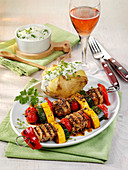 Vegetable skewers with pork fillet, served with baked potatoes and herb quark