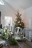 Festively set wooden table decorated in white, green and grey for Christmas meal