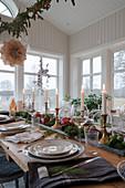 Centerpiece mit Kerzen, Granatäpfeln und Gemüse auf gedecktem Tisch