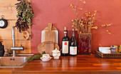 Schneidebrettchen, Wein und Trockenblumen in Holzvase