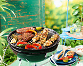 Pepper steaks and chicken kebabs on a grill