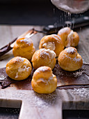 Sprinkling powdered sugar on profiteroles