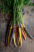 Different colored carrots on a wooden background