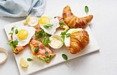 Croissants mit Spiegelei und geräuchertem Fisch, Salat und Sauce auf Marmorbrett