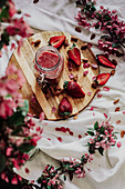 Glaskrug mit Erdbeersmoothie, umgeben von Erdbeeren und Blüten