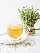 Thyme tea in a glass cup in front of a fresh bunch of thyme